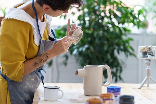 Garota vlogger faz vídeo-aula on-line sobre o processo de escultura em cerâmica, modelagem de tampa para jarro de cerâmica