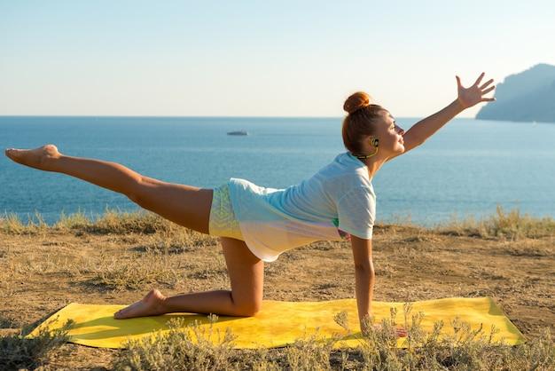 Garota yoga com fones de ouvido sem fio