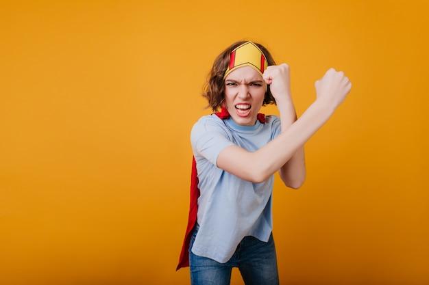 Garota zangada com coroa de brinquedo posando no espaço amarelo