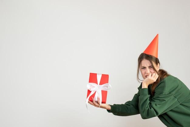 Garota zangada de frente com chapéu de festa segurando seu presente de natal