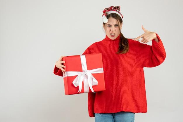 Garota zangada de frente com chapéu de papai noel segurando o dedo do presente e apontando para si mesma
