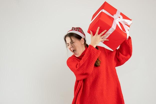 Garota zangada de frente com chapéu de papai noel segurando seu presente de natal