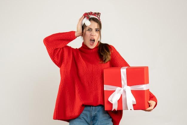 Garota zangada de frente com chapéu de papai noel segurando um presente segurando a cabeça em pé