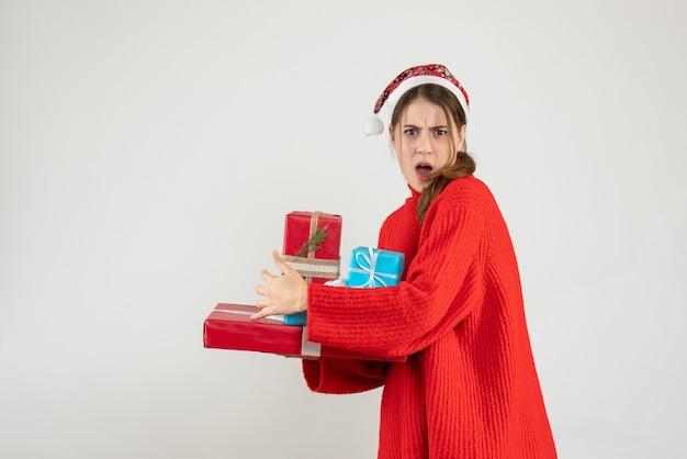 Garota zangada de frente com chapéu de papai noel tentando esconder seu presente de natal