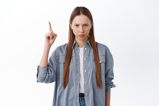 Garota zangada e amuada, carrancuda, apontando para uma coisa injusta, estar com ciúmes ou chateada, reclamando, decepcionada contra um fundo branco.