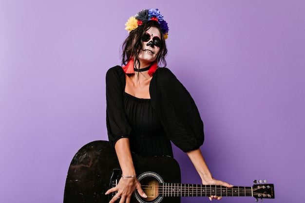 Garota zumbi animada tocando guitarra. mulher caucasiana maravilhosa em traje preto de halloween, se divertindo.