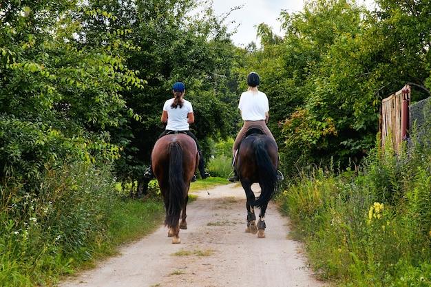 Garotas a cavalo andando em uma estrada rural vista traseira