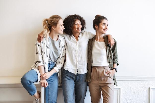 Garotas alegres em frente a uma parede branca dentro de casa