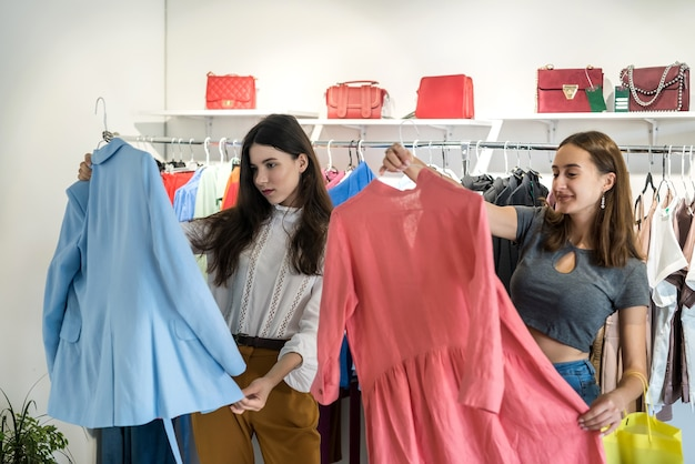 Garotas amigáveis passando tempo fazendo compras na loja de moda