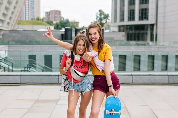 Garotas animadas com camisetas brilhantes aproveitando o fim de semana na pista de skate e posando com emoções felizes