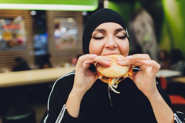 Garotas árabes no restaurante de fast-food comendo hambúrguer.