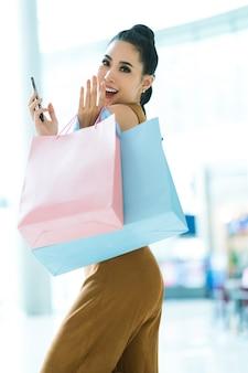 Garotas asiáticas estão se divertindo com suas compras. no shopping, ela tem sacolas de compras.