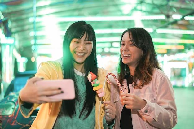 Garotas asiáticas felizes se divertindo fazendo selfie ao ar livre no parque de diversões