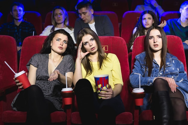 Garotas assistindo a um filme realmente chato no cinema.