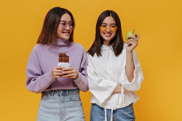 Garotas atraentes em óculos de sol coloridos posam na parede laranja isolada. menina com suéter roxo segurando uma barra de chocolate ao leite