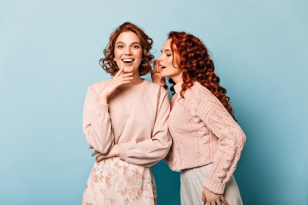 Garotas bem-humoradas falando sobre fundo azul. foto de estúdio de amigos alegres.