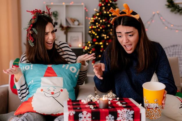 Garotas bonitas ansiosas com coroa de azevinho e bandana de rena olham para pipoca caída sentadas nas poltronas e aproveitando o natal em casa