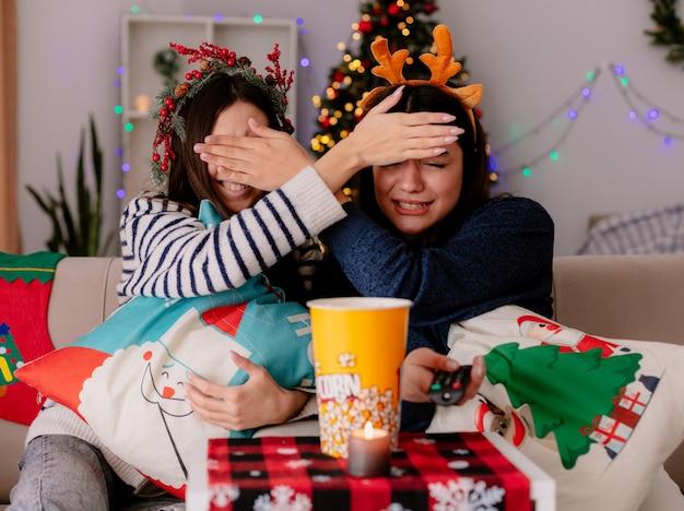 Garotas bonitas assustadas com coroa de azevinho e tiara de rena fecham os olhos com as mãos sentadas em poltronas na época do natal em casa