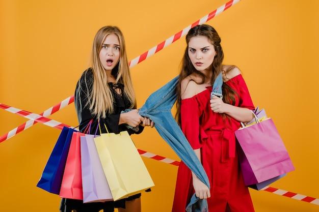 Garotas bonitas brigando por um par de jeans com sacolas coloridas e fita de sinal isolado sobre amarelo