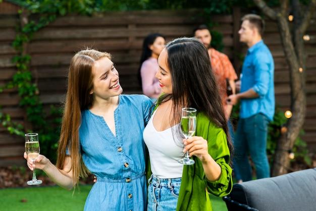 Garotas bonitas com bebidas olhando uns aos outros