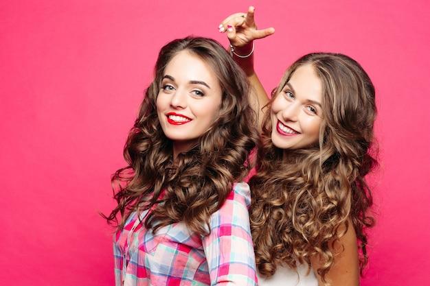 Garotas bonitas com cabelos cacheados e maquiagem após salão de beleza.