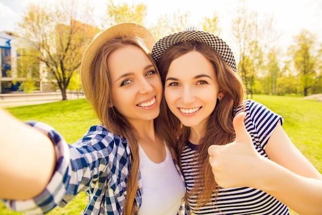 Garotas bonitas com sorrisos radiantes atirando e mostrando o polegar