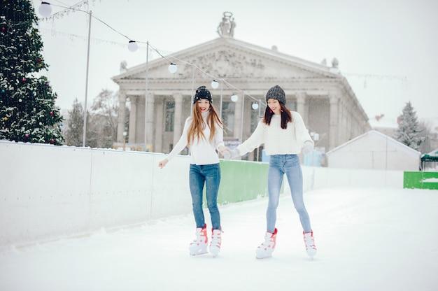 Garotas bonitas e bonitas com um suéter branco em uma cidade de inverno