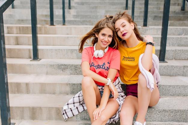 Garotas bonitas e elegantes descansando nas escadas após uma longa jornada pela cidade e sorrindo