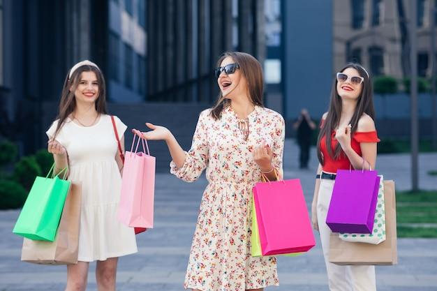 Garotas bonitas e felizes em vestidos casuais, blusa e calças saindo do shopping center com sacolas amarelas, verdes, roxas e rosa nas mãos após compras bem-sucedidas