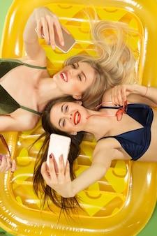 Garotas bonitas em traje de banho posando no estúdio.