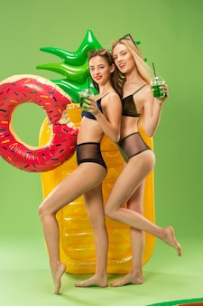 Garotas bonitas em trajes de banho posando no estúdio. adolescentes caucasianos do retrato de verão sobre fundo verde.
