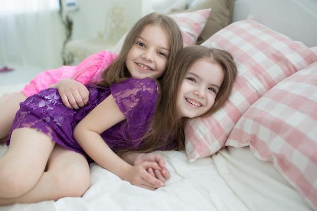 Garotas bonitas em vestidos cor de rosa e roxos deitar na cama