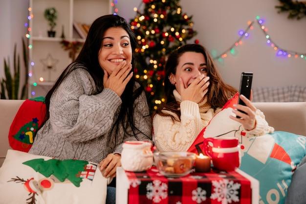 Garotas bonitas impressionadas olhando para o telefone sentadas em poltronas e curtindo o natal em casa