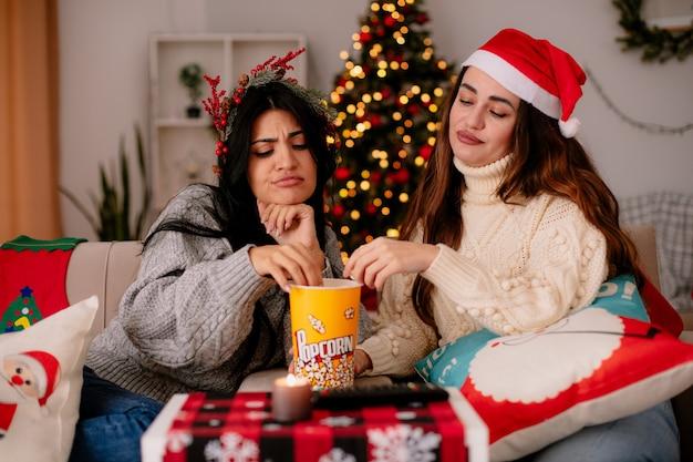 Garotas bonitas irritadas com chapéu de papai noel e coroa de azevinho comem e olham para o balde de pipoca sentadas nas poltronas na época do natal em casa