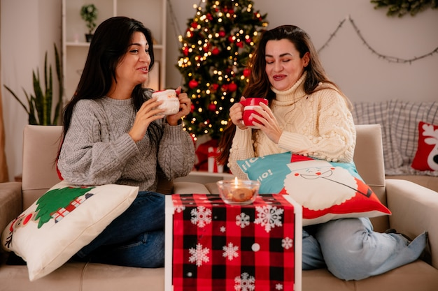 Garotas bonitas rindo segurando copos sentadas em poltronas e curtindo o natal em casa