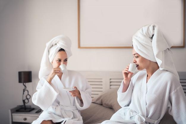 Garotas bonitas, tomando um café em um quarto de hotel