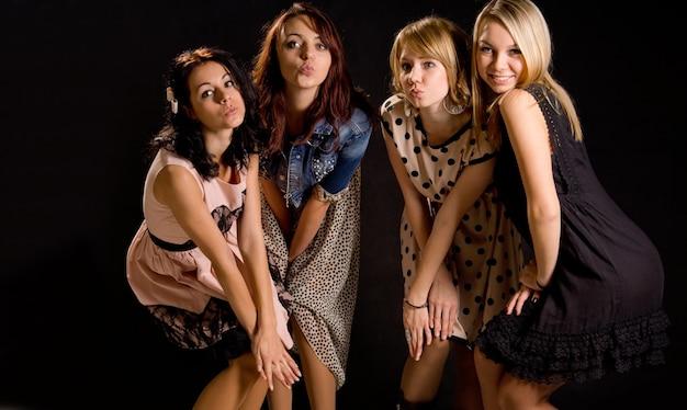 Garotas brincalhonas em trajes estilosos em fila, franzindo a boca como se estivessem se beijando