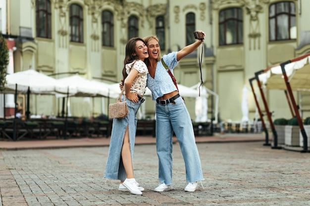 Garotas bronzeadas alegres e felizes abraçam e tiram selfie ao ar livre usando uma câmera retro