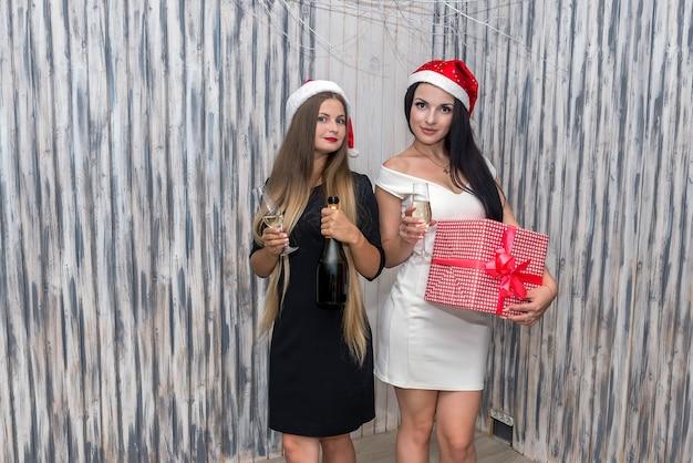 Garotas com champanhe e caixa de presentes em estúdio