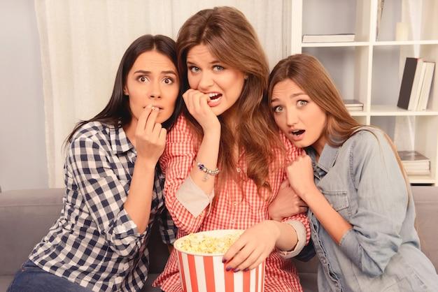Garotas com medo assistindo filme e comendo pipoca