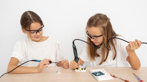 Garotas com óculos de proteção fazendo experimentos científicos juntas