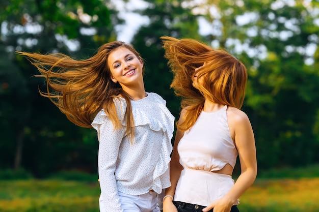Garotas com roupas lindas balançam os cabelos contra o fundo da natureza
