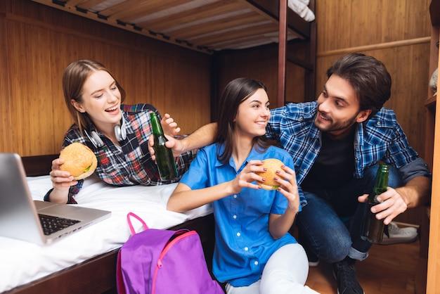 Garotas comem hambúrgueres e homem serve cerveja no quarto.