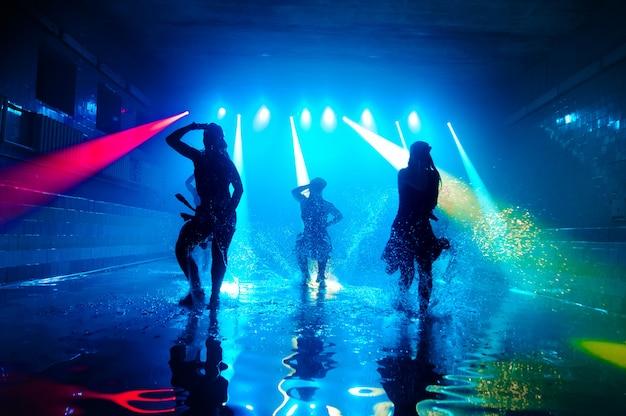 Garotas dançando na água com uma bela luz.