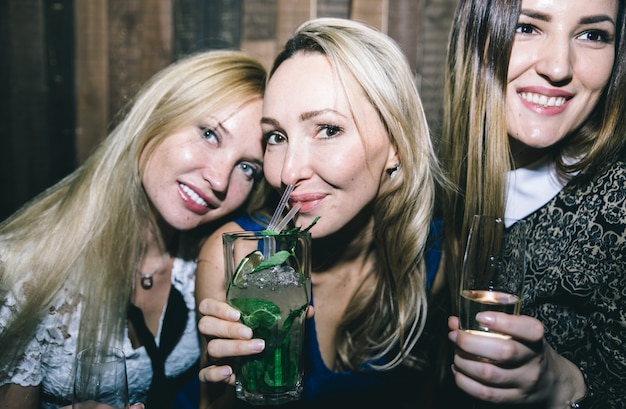 Garotas de festa em um restaurante comemorando com bebidas e champanhe