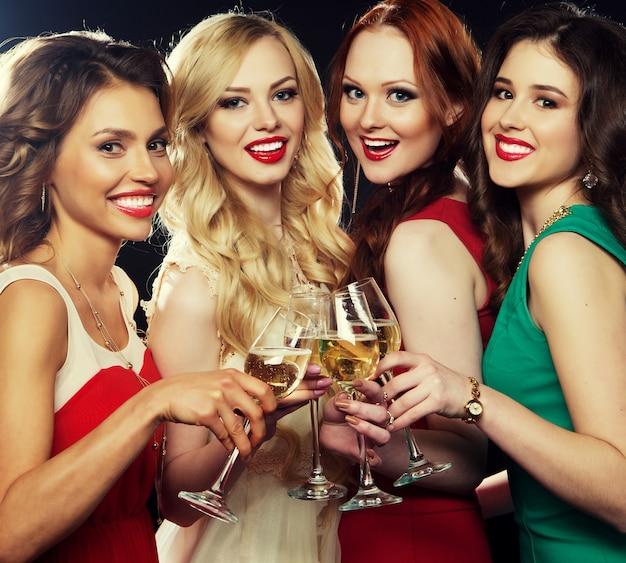 Garotas de festa tinindo flautas com vinho espumante