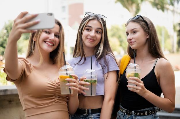 Garotas de tiro médio com bebidas e tirando selfie