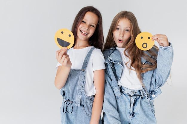 Garotas de tiro médio segurando emojis