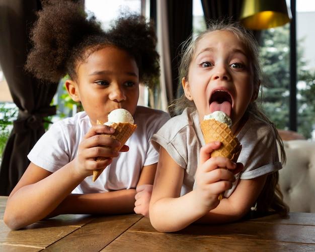 Garotas de tiro médio tomando sorvete