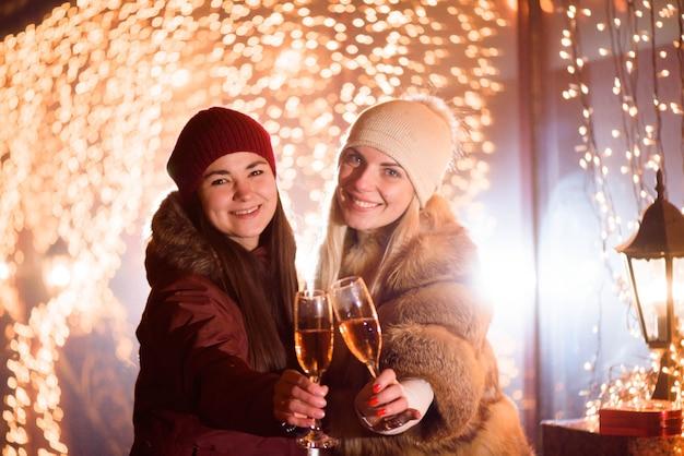 Garotas desfrutando de champanhe. retrato ao ar livre de senhoras sobre fundo claro.